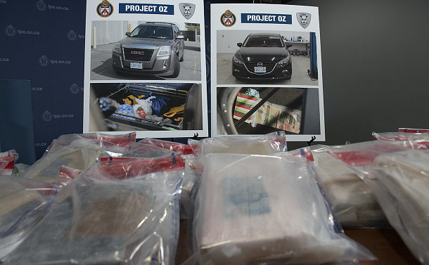 Substances wrapped in plastic in front of photos of a car and trunk and compartments within them