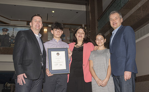 Two men and a woman with a boy holding a framed certificate and a girl