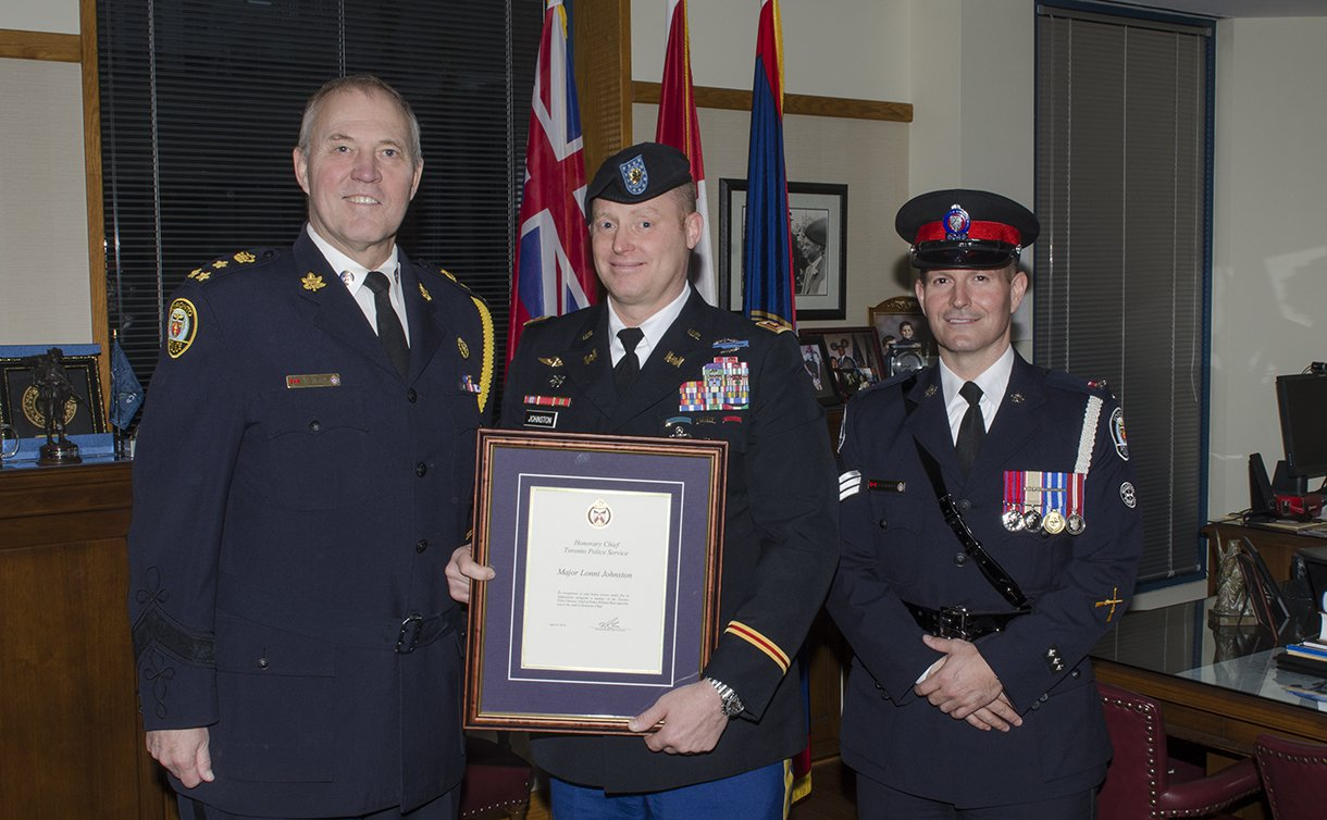 Two men in TPS uniform on either side of a man in U.S. military uniform holding a framed certificate
