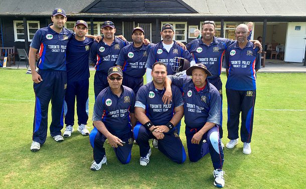 Toronto Police Cricket Club members in front of the pavilion in blue cricket uniforms.