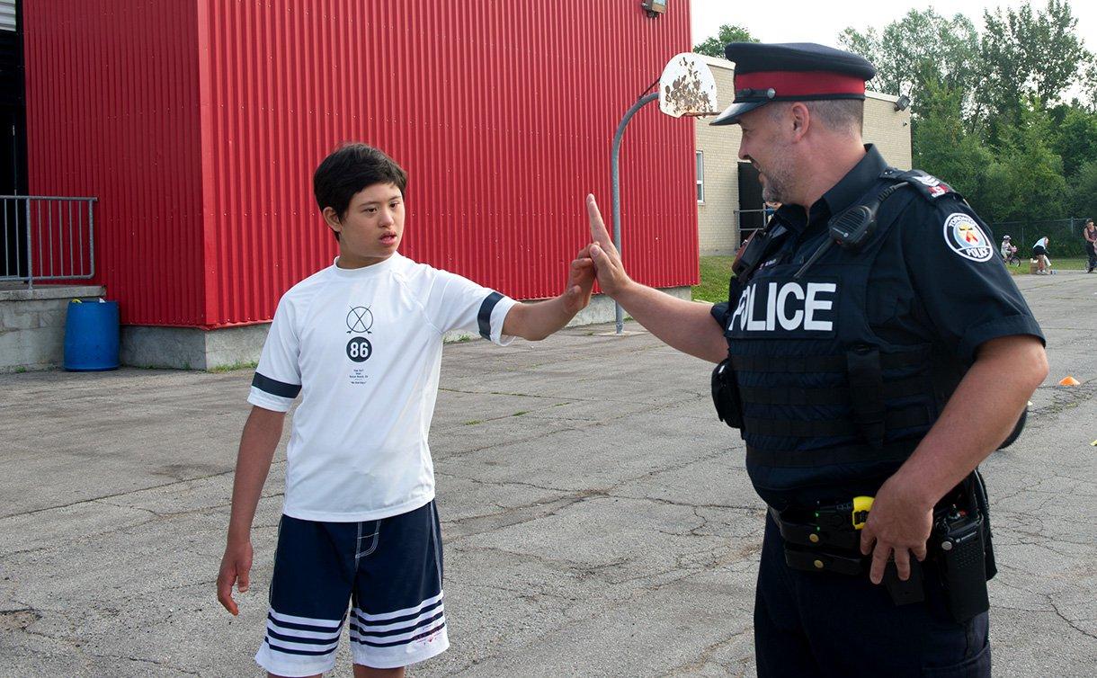 A boy gives a man in uniform a high-five