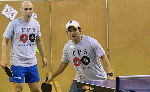 A man watches as another man hit a ball with table tennis racket
