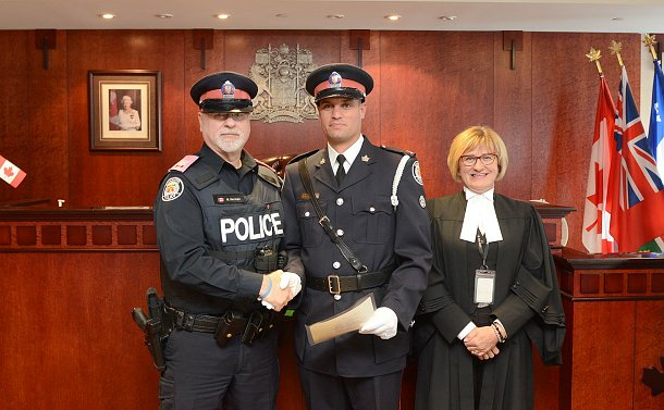 Two men in TPS uniform with a woman in a black robe