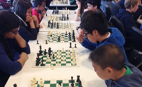 Elementary school students playing chess