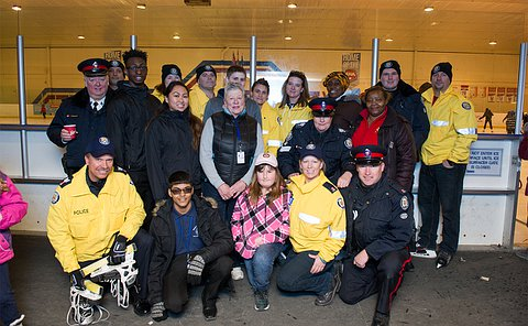 Officers in uniform, some with skates in their hands, alongside community members pose for a photograph outside an ice rink.
