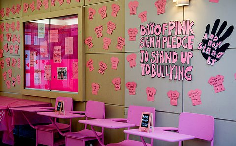 A hallway filled with pink anti-bullying signs.