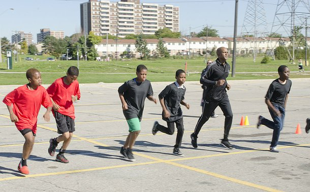 A man in a TPS track suit runs alongside a group of boys