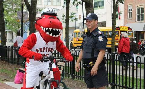 The Raptors mascot on a bicycle beside a man in TPS uniform