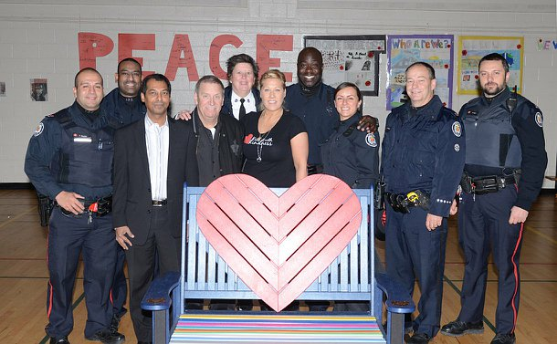 A group of people, some in TPS uniform stand behind a large blue bench with a  heart in the centre of the back support