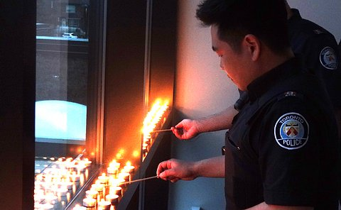 Two men in TPS uniform lighting tea lights