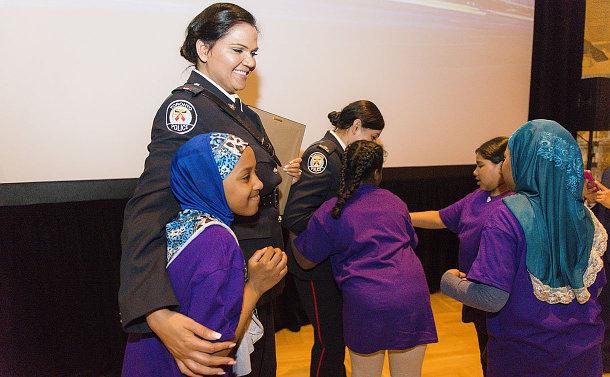 A girl hugging a woman in TPS uniform