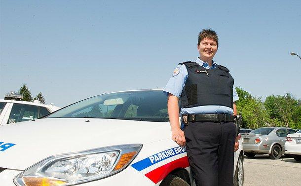 A woman in TPS Parking uniform beside a parking vehicle