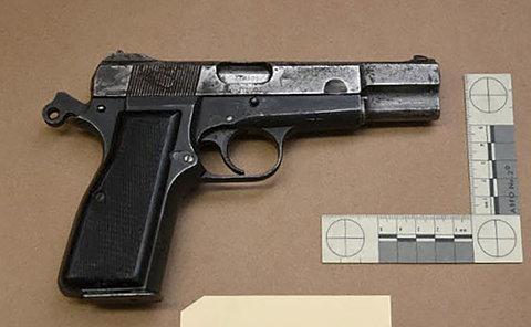A black handgun on a table beside a ruler