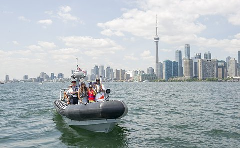 A group of people, one in TPS uniform, stand in a boat with Toronto skyline in background