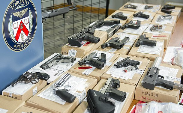 A table full of firearms lay on boxes near a TPS logo