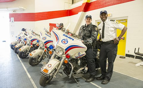 A row of TPS motorcycles beside a woman in TPS uniform and a man in TPS auxiliary uniform