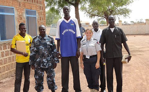 Five men in various clothing stand with a woman in a Toronto Police uniform
