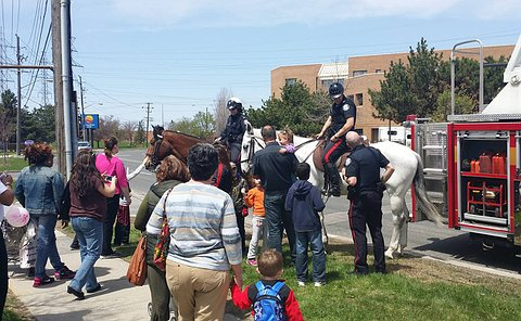 Adults and children gather around two men in TPS uniform on horses