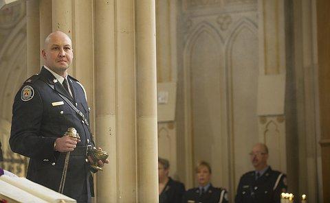 A man in TPS uniform stands beside a stone pillar