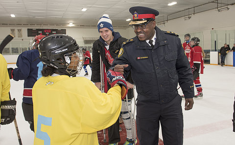 A man in police uniform fist bumps a girl in hockey uniform