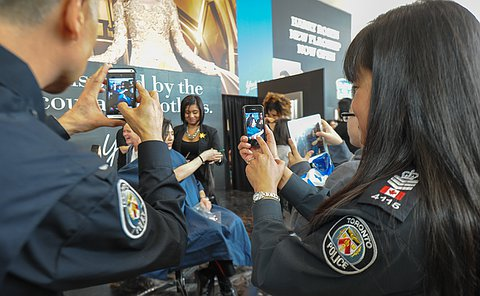 A man and woman in TPS uniform take photos on their phones of a woman sitting in a chair having her hair cut by another woman