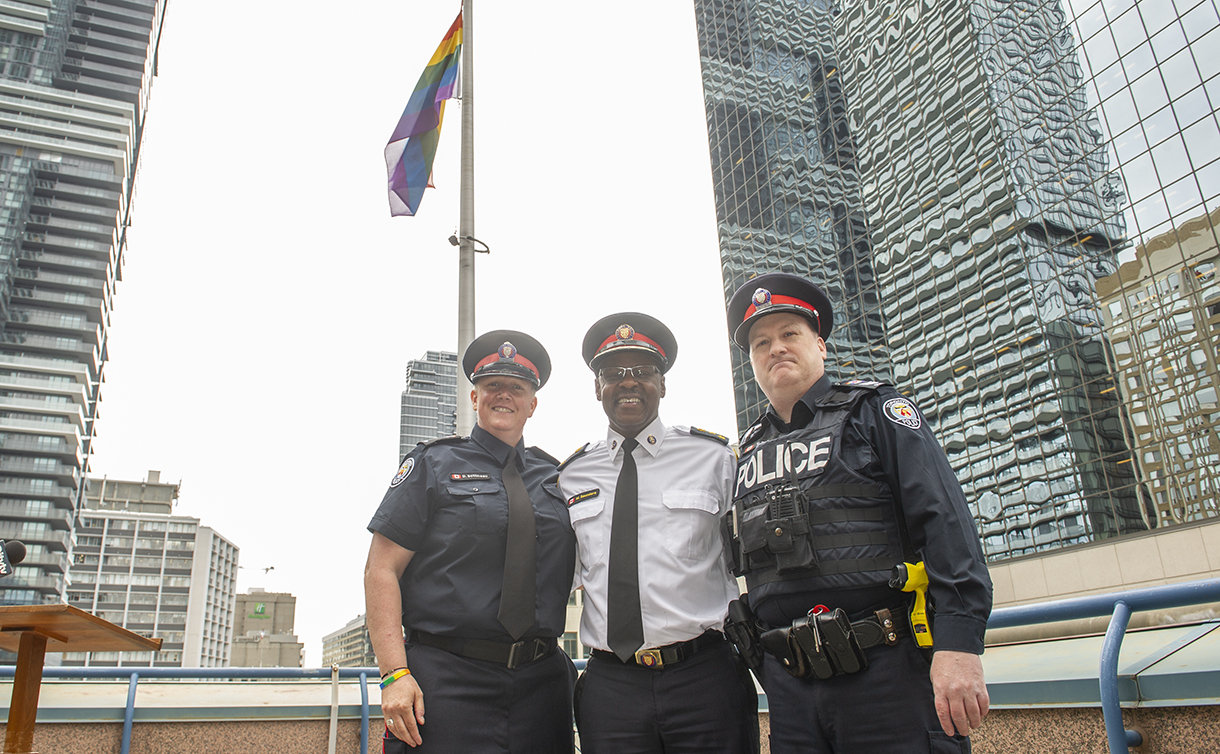 A woman and two men in TPS uniform under a Pride flag