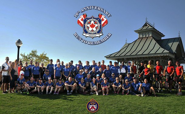 A large group of men and women in blue and red T-shirts on grass near a gazebo