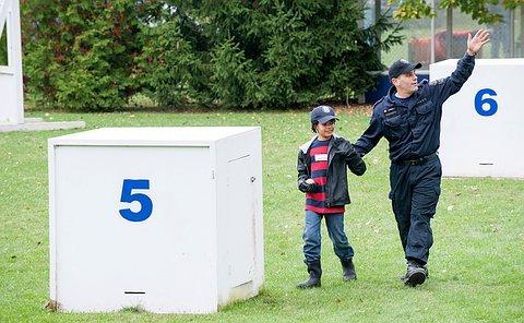 A boy and an officer walk towards a big wooden box with an open door.