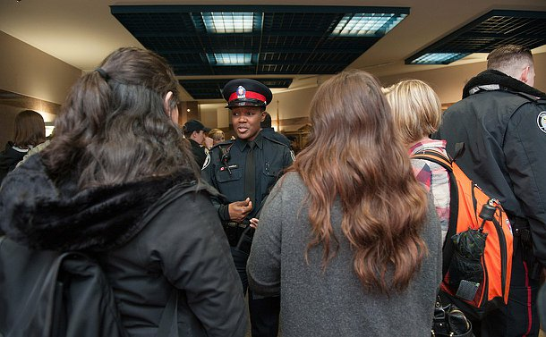 A female officer in uniform speaking to students. the students backs are to the camera.