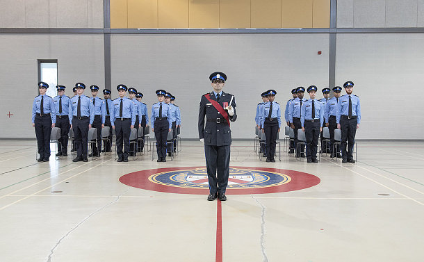 A group of TPS court officers in uniform at attention