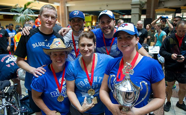 Five people in blu clothing holding a large trophy and smiling.