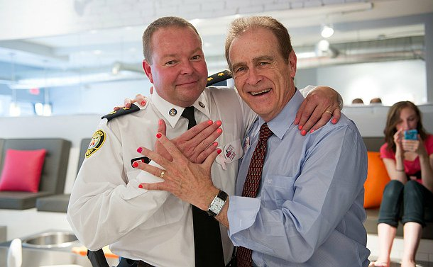 Two men, on in a dress shirt and tie the other in police uniform with their hands raised up to show pink nail plush on their finger nails.