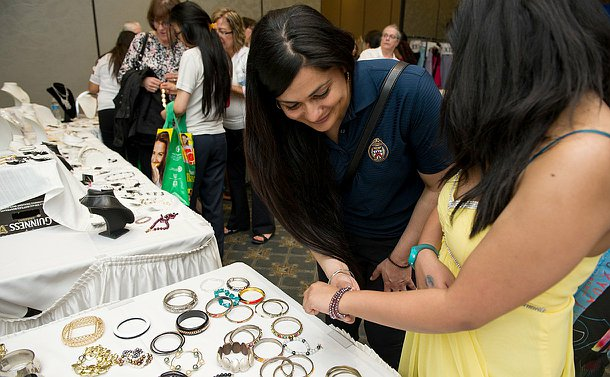 A woman looks down at a bracelet on a girl's wrist near a table of jewellery