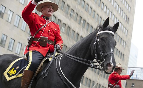 A man in a RCMP uniform rides on horseback and waves to crowd