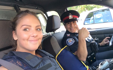 Two women in a police vehicle, one in uniform