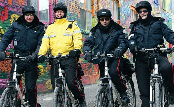 Four officers in TPS uniform on bicycles in an alley