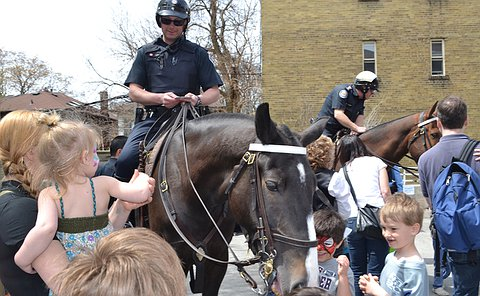 A man in TPS uniform on a horse surrounded by adults and children