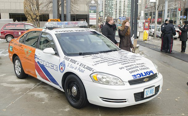 A car with decals and colours of Beck Taxi on the rear end and Toronto police scout car on the front end with lettering describing costs due to impaired driving on hood
