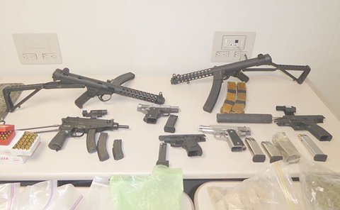 A table with several handguns and long guns