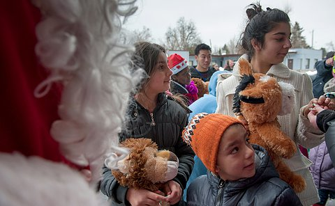 Three children, one holding a bear, standing around a man dressed as Santa Claus.