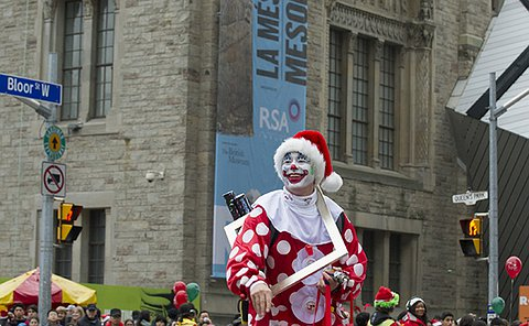 A man dressed as a clown walk down street in front of crowd