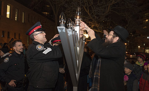 A man in TPS uniform beside another man lighting a candle on a large metal stand