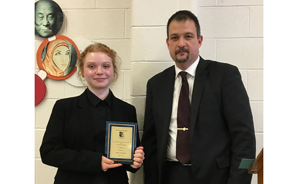 A girl holding a plaque with a man