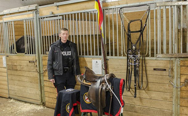 A man in TPS uniform in a stable