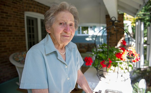 An elderly woman standing on her porch, looking at the camera, in the background there are flowers with some sunlight falling on to them.