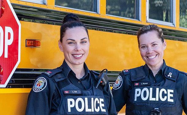 Two women in TPS uniform by a school bus