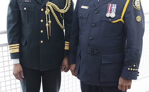 One man in military uniform standing to left of man in TPS uniform