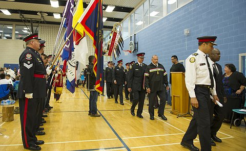 A group of officers in TPS uniform walk past flag bearers
