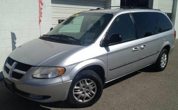 Silver minivan in front of a garage