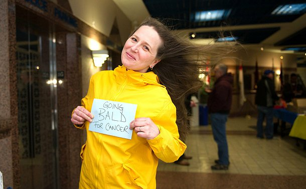 "A woman in a yellow wind breaker with a fan blowing her hair outwards, she is holding a sign that reads ""going bald for cancer."""